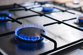 Gas kitchen stove cook with blue flames burning