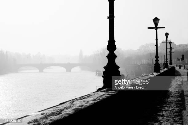 gas lights by river against clear sky during foggy weather - ガス燈 ストックフォトと画像