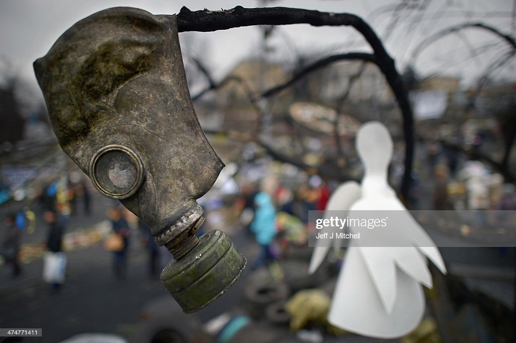 A gas mask hangs in a tree along with a paper angel in Independence Square where dozens of protestors were killed in clashes with riot police last week on February 25, 2014 in Kiev, Ukraine. Ukraine's interim President Olexander Turchynov is due to form a unity government, as UK and US foreign ministers meet to discuss emergency financial assistance for the country.