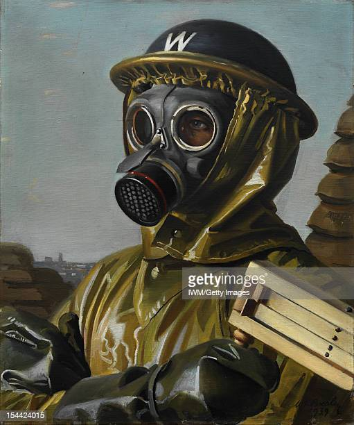 Gas Mask Head and shoulders of an airraid warden in helmet and gas mask a gasattack wooden rattle held in his glovedright hand circa 1939