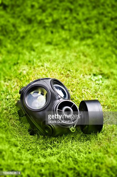 gas mask on grass - gas mask stock pictures, royalty-free photos & images