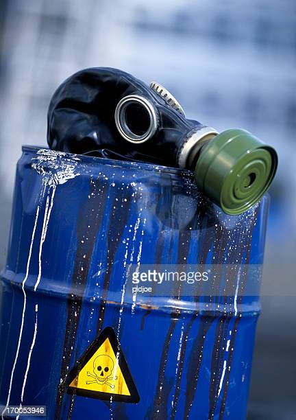 gas mask on leaking barrel with toxic waste