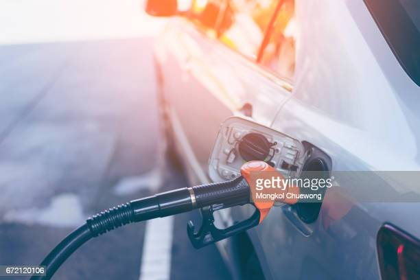 Gas nozzle pumping gas into a gray blonde car