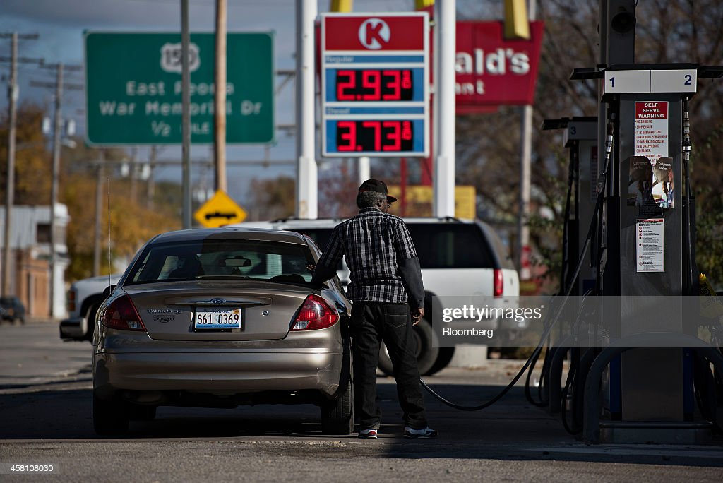 Gas prices are displayed as a customer fuels a vehicle at a