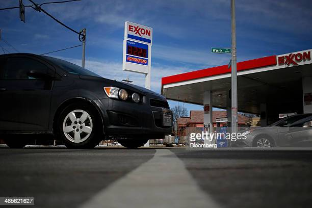 Gas prices are displayed as cars drive past an Exxon Mobil Corp station in Cincinnati Ohio US on Monday Jan 27 2014 Exxon Mobil Corp is scheduled to...