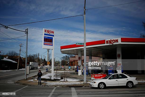 Gas prices are displayed on a sign as a car drives past a pedestrian standing on the corner near an Exxon Mobil Corp station in Cincinnati Ohio US on...
