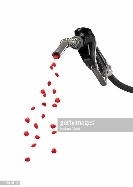 Gas pump nozzle spraying out red heart shape candies