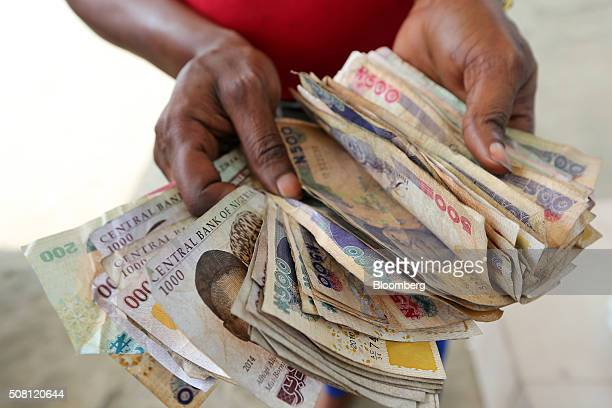 A gas station attendant displays a large bundle of naira banknotes after selling fuel to a customer in Port Harcourt Nigeria on Friday Jan 15 2016...
