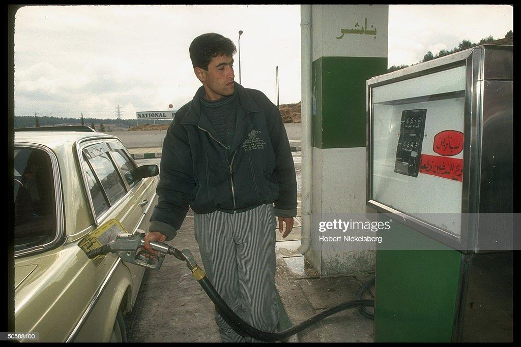 Gas station attendant manning pump, fill : News Photo