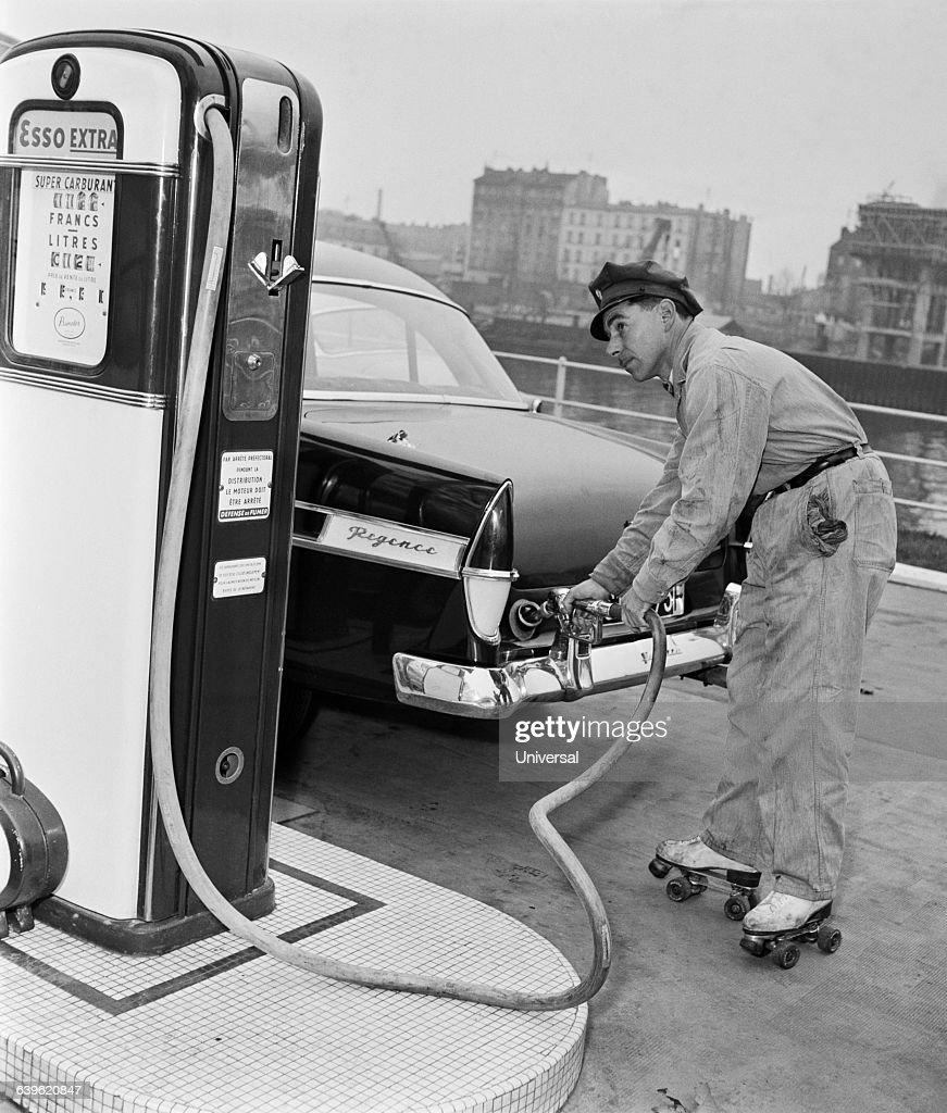 gas-station-attendant-on-roller-skates-fills-the-tank-of-a-car-picture-id639620847