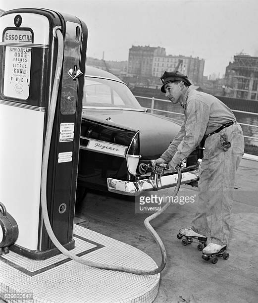 A gas station attendant on roller skates fills the tank of a car