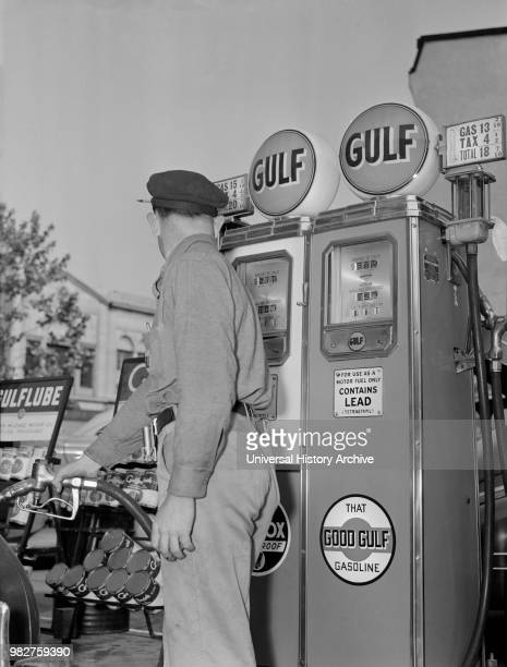 Gas Station Attendant Pumping Gas while Keeping an eye on Gauge during Gasoline Rationing USA Office of War Information 1940's