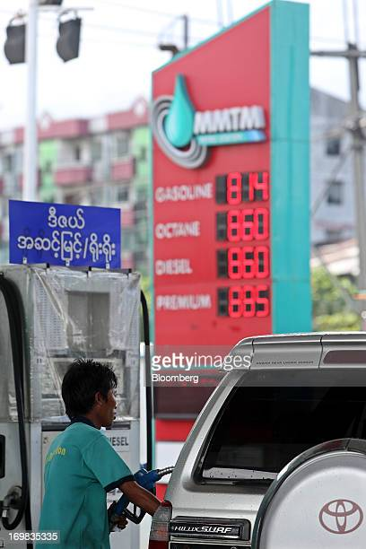 A gas station attendant refuels a Toyota Motor Co Hilux Surf offroad vehicle at an MMTM gas station in Yangon Myanmar on Sunday June 2 2013 Myanmar...
