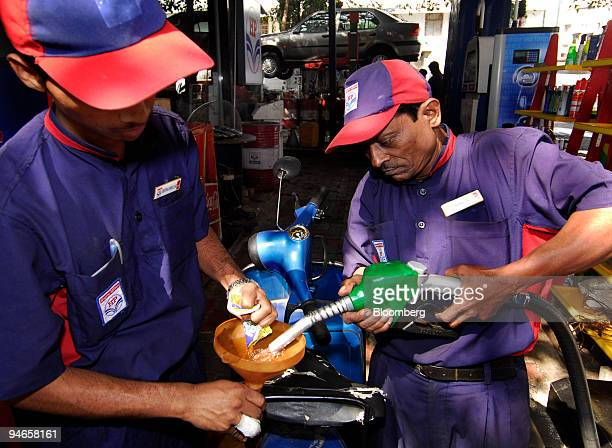 Gas station attendants add fuel to a motorbike in Mumbai India on Thursday Nov 29 2007 India's economy grew last quarter at the slowest pace since...