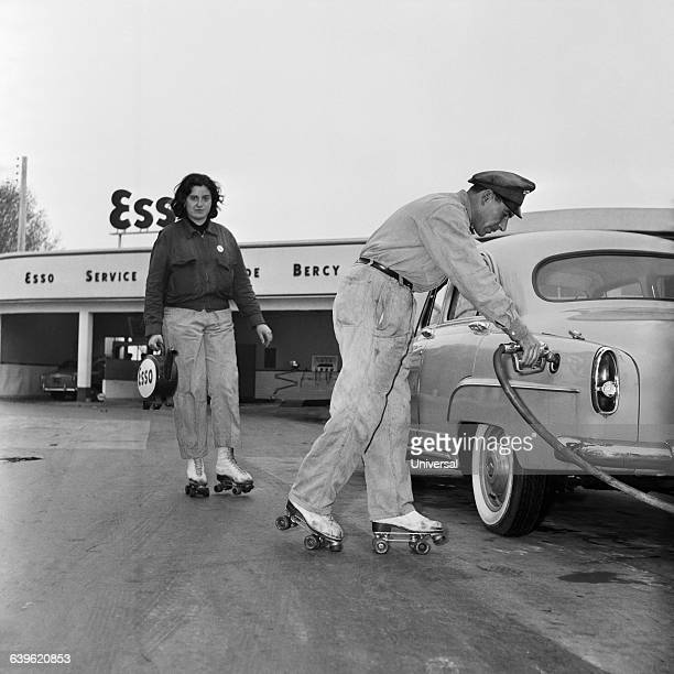 Gas station attendants on roller skates fill the tank of a car