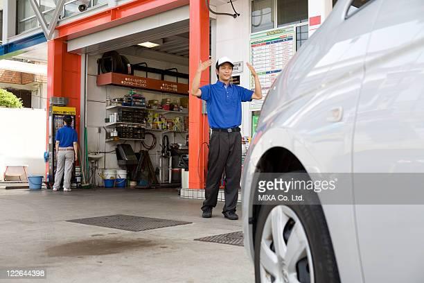 Gas station clerk guiding car