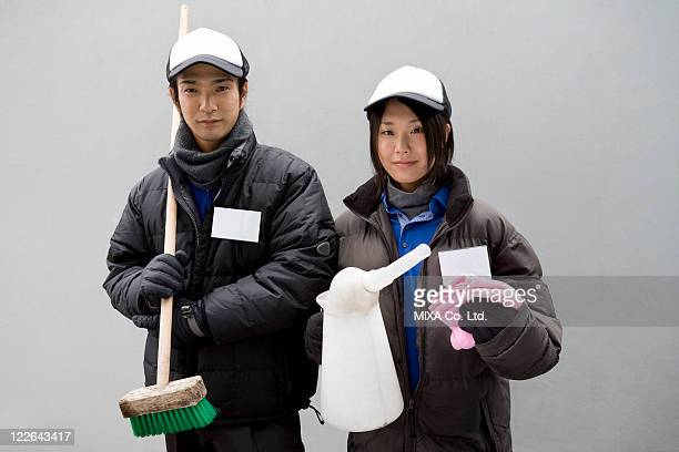 Gas station clerk holding cleaning goods
