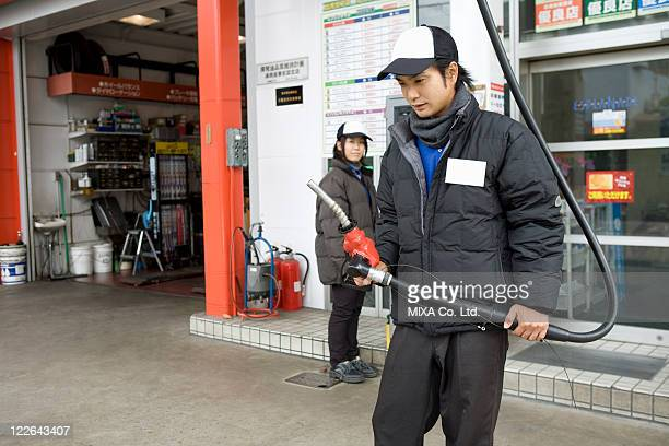 Gas station clerk holding nozzle