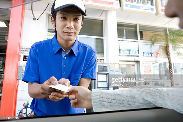 Gas station clerk receiving card from customer