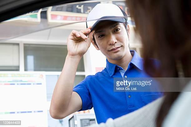 Gas station clerk welcoming customer