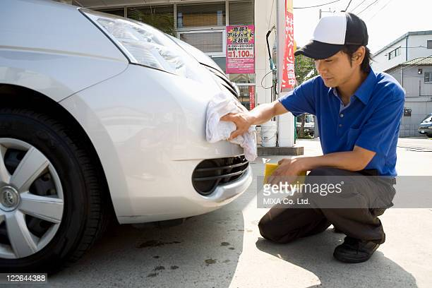 Gas station clerk wiping car