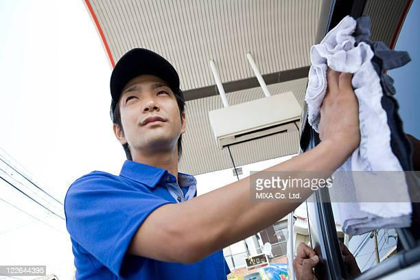 Gas station clerk wiping car window