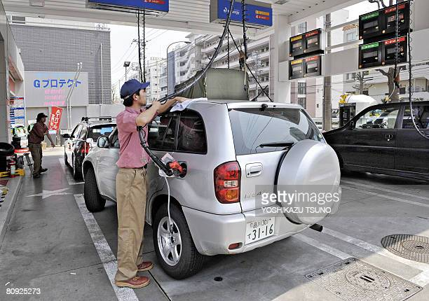 A gas station employee refuels a vehicle at a Tokyo gas station on April 30 2008 as oil prices will rise from May 01 Japan's ruling coalition rammed...