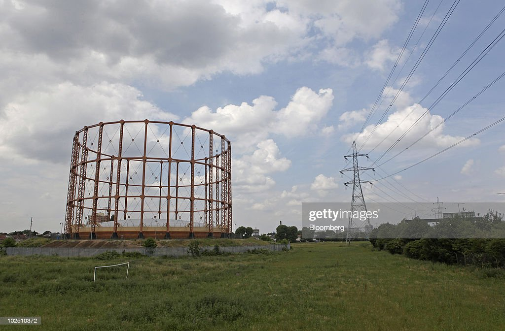A Gas Storage Tank Stands Next To An Electricity Pylon In London U K On
