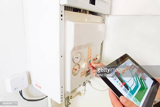 Gas technician checking installations with tablet.