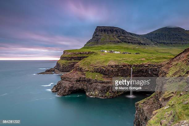 Gasadalur, Vagar island, Faroe Islands, Denmark. The iconic waterfall jumping from the cliff into the ocean.