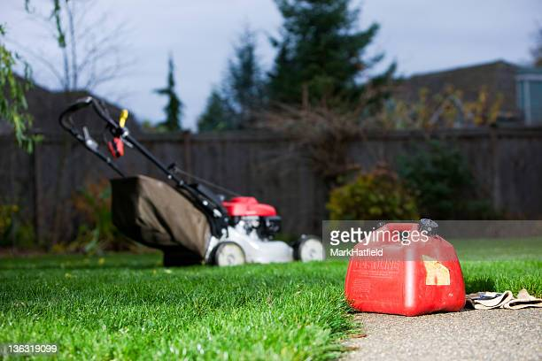 gasoline can with mower in background - lawn mower stock pictures, royalty-free photos & images