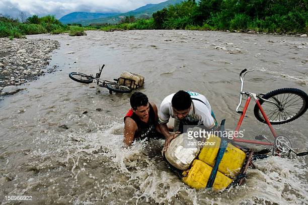 Gasoline smugglers with their contraband fell into the water of the river Táchira on the Colombian-Venezuelan border, 3 May 2006. One load of...