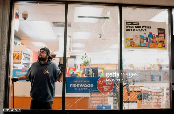 A gasoline station attendant cleans up broken glass from an explosion in Houston Texas on January 24 2020 A large explosion shook the US city of...