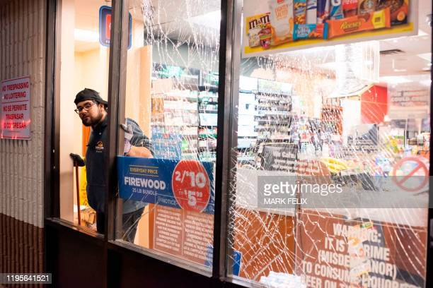 Gasoline station attendant cleans up broken glass from an explosion in Houston, Texas, on January 24, 2020. - A large explosion shook the US city of...