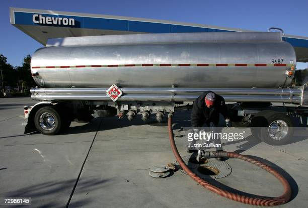 A gasoline tanker truck driver attaches a hose to an underground tank at a Chevron service station January 12 2007 in Greenbrae California Despite...