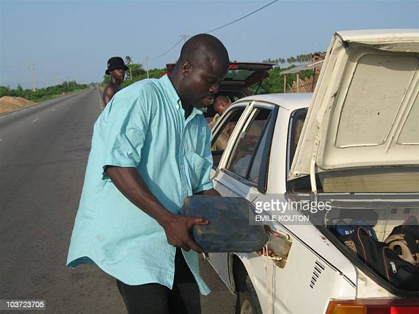 A gasoline traffickers fills the gas tank of a taxi 02 June 2006 at the Illacondji border separating Benin and Togo some 100 kms west of Cotonou...