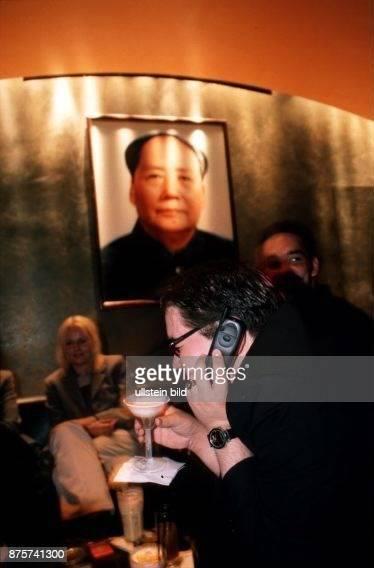 Gast in der LützowBar sitzt unter einem Mao Bild und telefoniert den Cocktail in der einen Hand mit einem Handy 1999