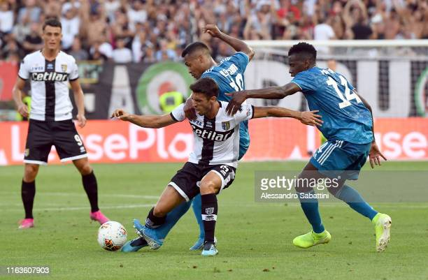 Gaston Brugman of Parma Calcio competes for the ball with Alex Sandro of Juventus during the Serie A match between Parma Calcio and Juventus at...