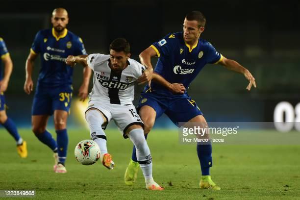 Gaston Brugman of Parma Calcio competes for the ball with Valerio Verre of Hellas Verona during the Serie A match between Hellas Verona and Parma...