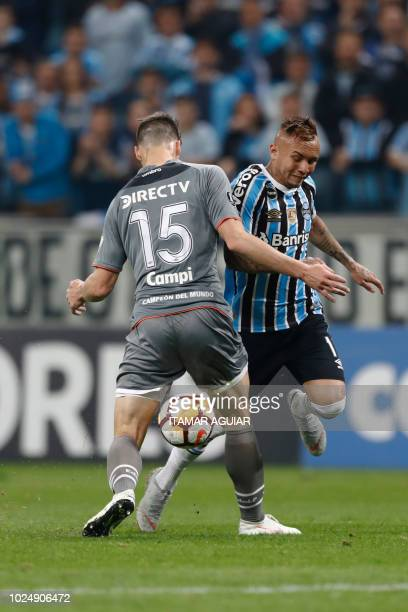 Gaston Campi of Argentina's Estudiantes vies for the ball with Everton of Brazil's Gremio during their Copa Libertadores 2018 football match held at...