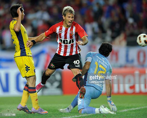 Gaston Fernandez of Estudiantes struggles for the ball with Diego Barrero goalkeeper of Cerro Porteno and missing an opportunity to score during a...
