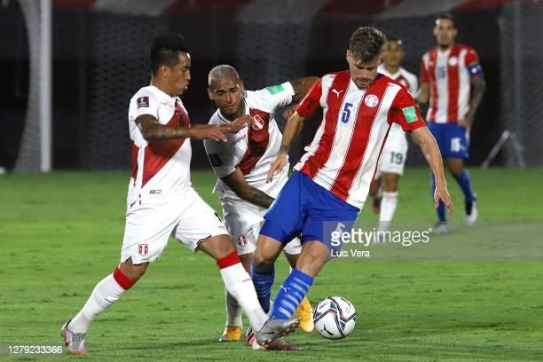Gaston Gimenez of Paraguay fights for the ball with Christian Cueva and Miguel Trauco of Peru during a match between Paraguay and Peru as part of...