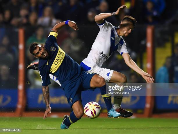 Gaston Gimenez of Velez Sarsfield fights for the ball with Carlos Tevez of Boca Juniors and gives penalty foul during a match between Boca Juniors...