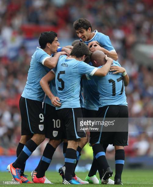 Gaston Ramirez of Uruguay is congratulated by team mates after scoring a goal during the Men's Football first round Group A Match of the London 2012...