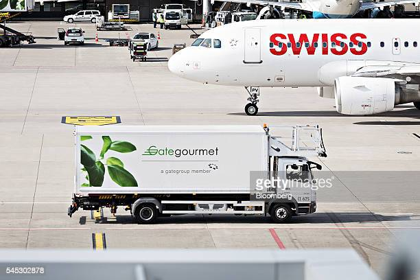 A Gate Gourmet International AG catering truck passes by a passenger aircraft operated by Swiss International Air Lines AG at Zurich Airport operated...