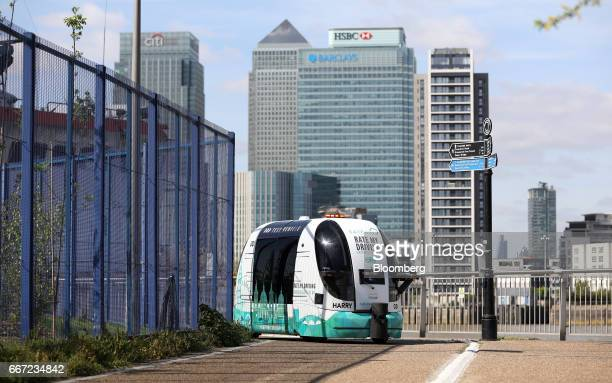 GATEway autonomous pod, operated by TRL Ltd., passes along a walkway against a backdrop of the Canary Wharf financial, business and shopping district...