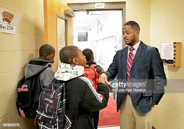 Gateway Elementary School fifth grader Clarence Boykins III center shakes hand with teacher Jim Triplett at the start of the school day on Thursday...