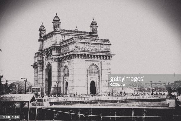 Gateway of India with a steam of tourists walking around it.