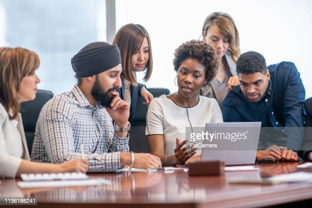 gathered around a laptop - businesswear stock pictures, royalty-free photos & images