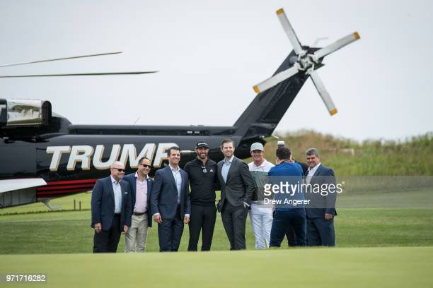Gathered at center Eric Trump and Donald Trump Jr pose for photos with professional golfer Dustin Johnson before a ribbon cutting event for a new...
